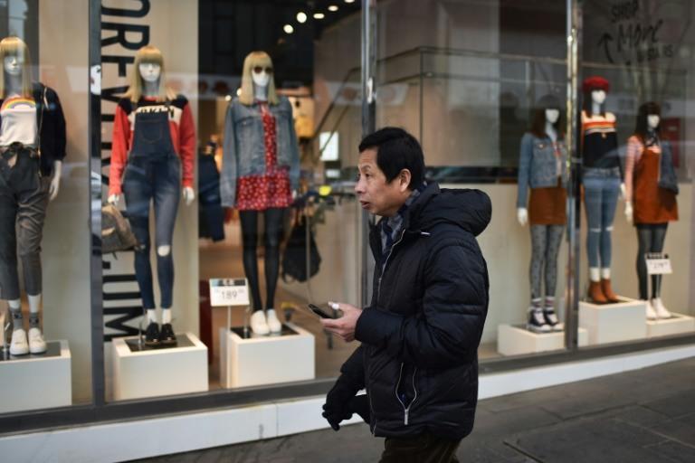 رجل يمر أمام محلات تجارية في بكين