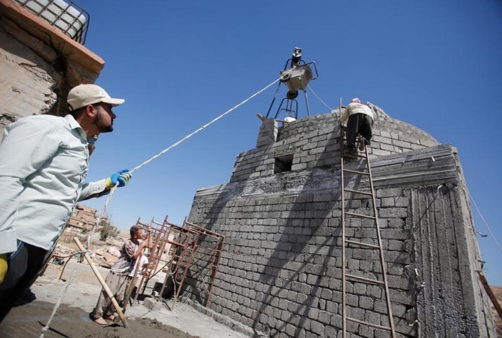 عمال يعيدون بناء بناية دمرها تنظيم الدولة افسلامية في قرية قرب الموصل