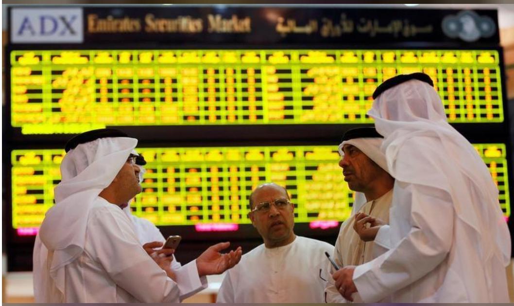 مستثمرون أمام لوحات إلكترونية تعرض مؤشرات الأسهم في بورصة أبوظبي