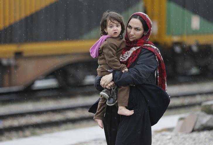 مهاجرة أفغانية تحمل طفلا على الحدود بين مقدونيا وصربيا - أرشيف رويترز