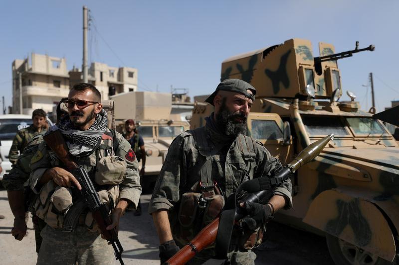 مقاتلون من قوات سوريا الديمقراطية يقفون بجوار مركبة عسكرية في مدينة الرقة بشمال سوريا
