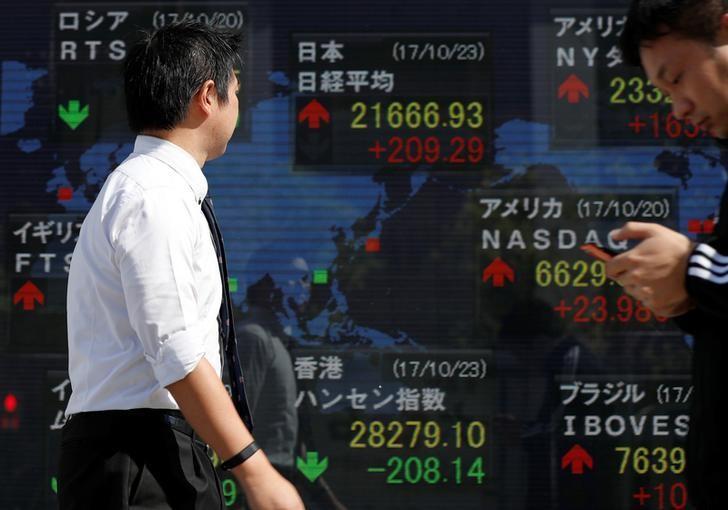 رجل يمر بلوحة إلكترونية تعرض مؤشرات الأسواق في طوكيو