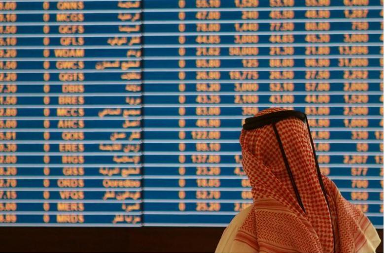 متعامل في بورصة قطر يتابع شاشة إلكترونية تعرض أسعار الأسهم في صورة  أرشيفية