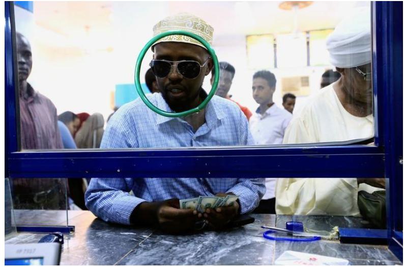 رجل يمسك دولارات بمكتب للصرافة في الخرطوم