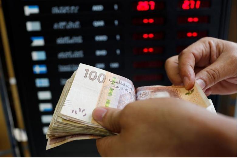 أحد العاملين يعد أوراق نقد فئة 100 درهم بمكتب للصرافة في الدار البيضاء