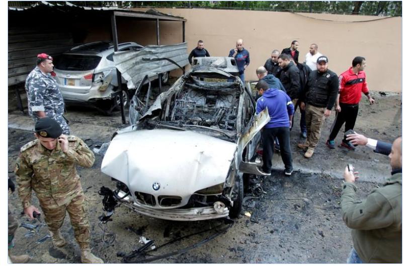 أشخاص يفحصون سيارة مسؤول بحماس تعرضت لانفجار في صيدا بلبنان
