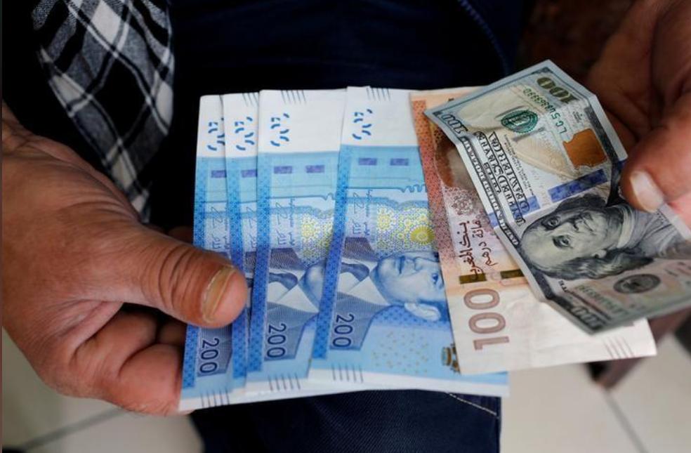 ورقة نقدية فئة 100 دولار أمريكي وأوراق نقدية بالدرهم المغربي في الدار البيضاء