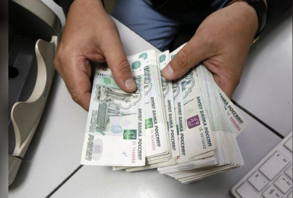 رجل يعد أوراقا نقدية فئة الروبل الروسي في سيبريا.