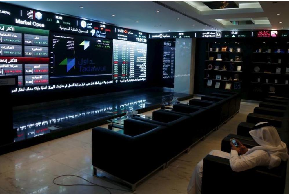 متعامل يجلس أمام شاشات تعرض أداء الأسهم في البورصة السعودية بالرياض