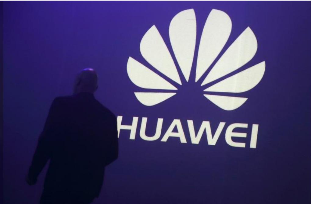 رجل يمر بجانب شعار شركة هواوي الصينية في باريس