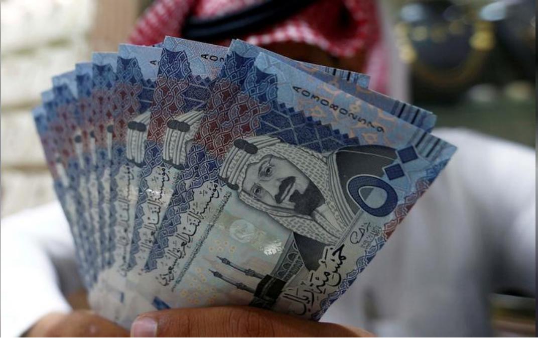 صراف سعودي يعرض أوراق نقدية من فئة 500 ريال سعودي في صرافة في الرياض