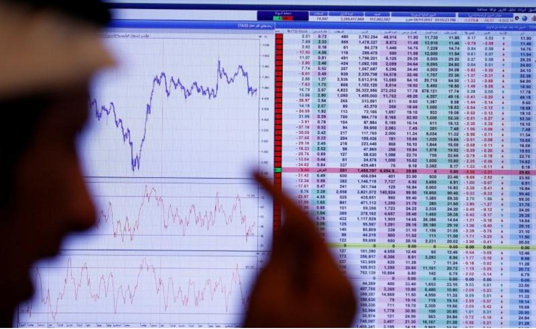 مستثمر ينظر الى شاشة تعرض معلومات عن الأسهم في الرياض