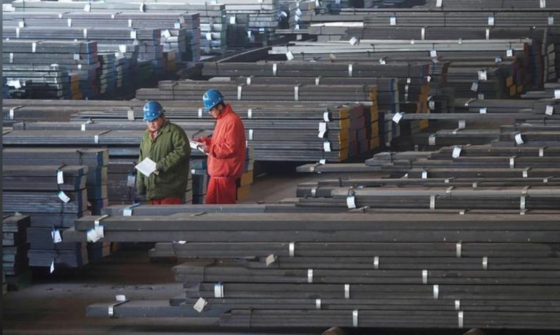 عاملان يفحصان قضبان الصلب في مصنع بالصين