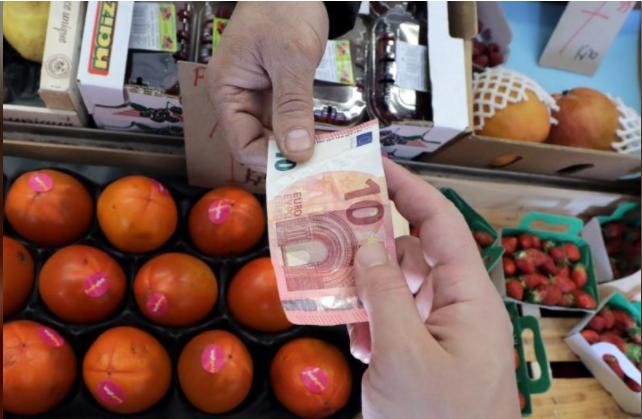 رجل يدفع المال لبائع فاكهة في سوق بمدينة نيس في فرنسا