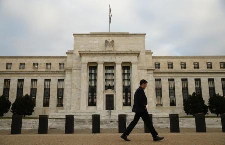 رجل يمر بجوار البنك المركزي الأمريكي في واشنطن