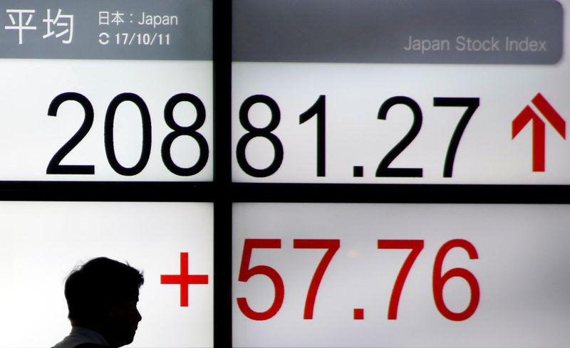 رجل يمر أمام لوحة الكترونية تعرض مؤشر نيكي القياسي في طوكيو