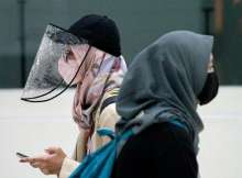 Women are pictured wearing a protective face mask and face shield in Jakarta