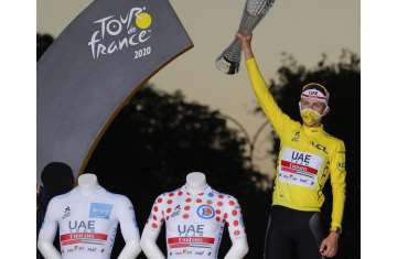 Tour de France winner Slovenia's Tadej Pogacar, wearing the overall leader's yellow jersey, celebrates on the podium after the twenty-first and last stage of the Tour de France cycling race over 122 kilometers (75.8 miles)
